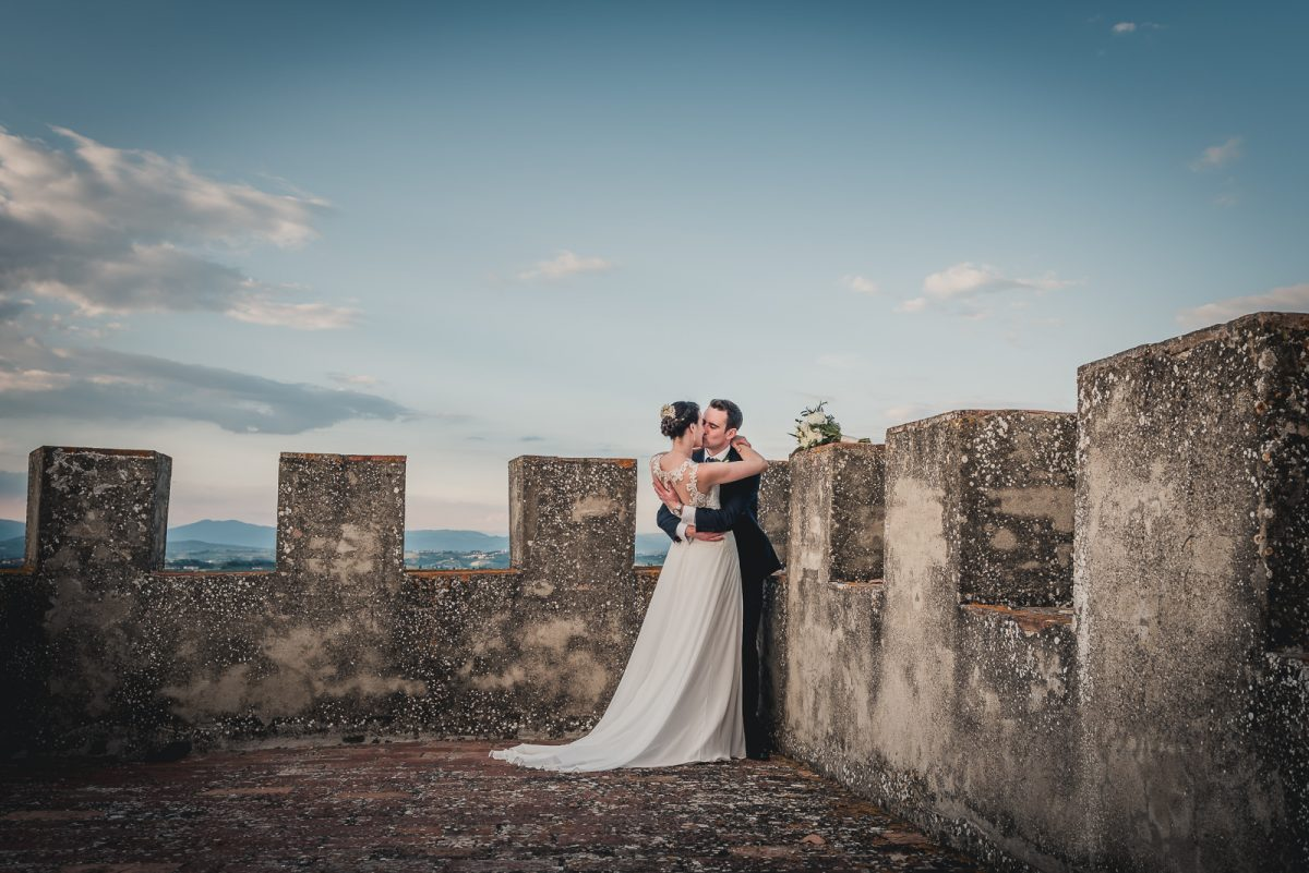 Couple hugging at the top of a castle tower in Florence Italy