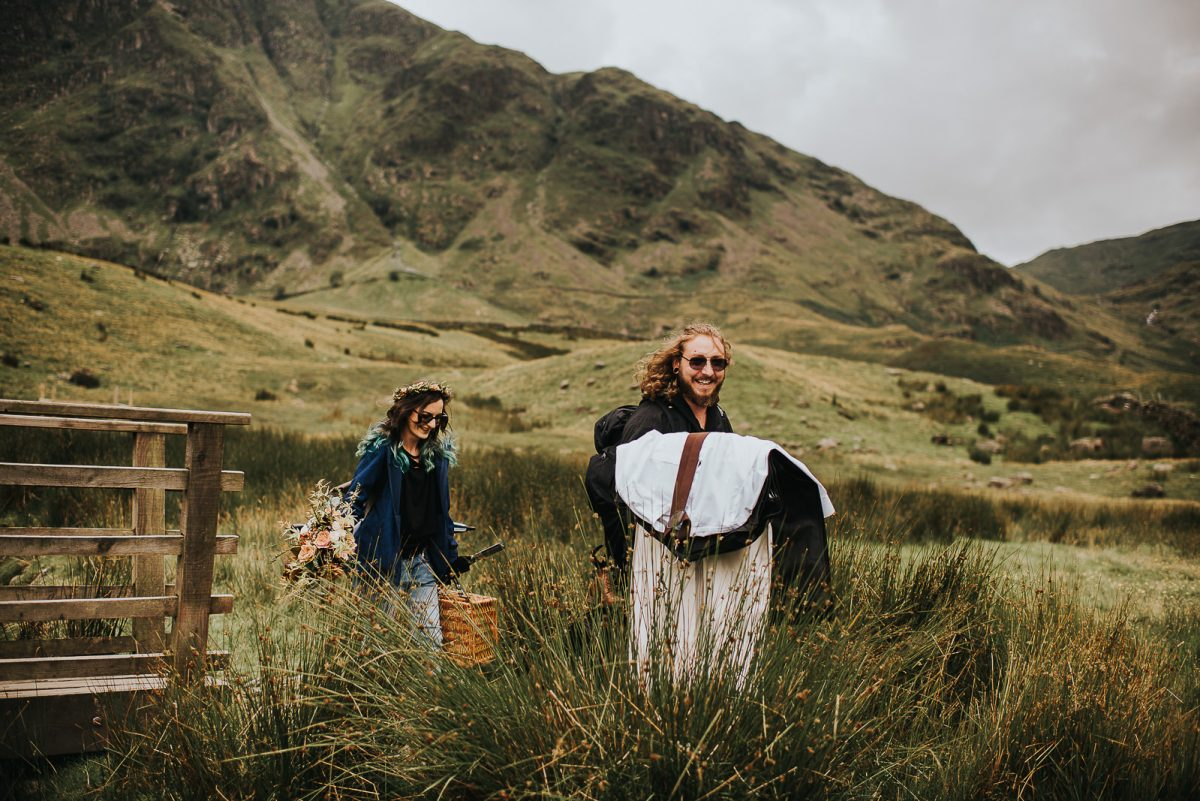 Couple hiking towards the ceremony spot for their elopement. The groom is carrying the clothes, the bride is carrying food for a celebration picnic