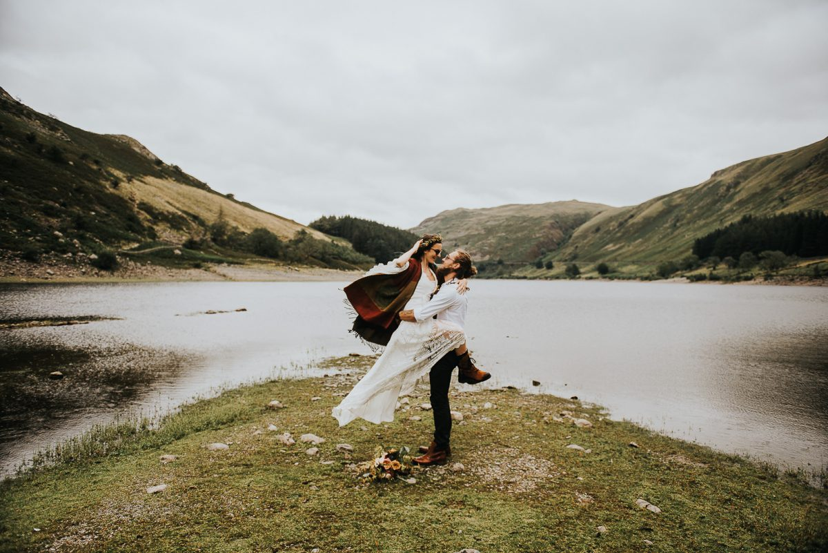 Groom holding the bride, in front of a lake. The bride is wearing a boho wedding dress, a wool cloak, and a flower crown.