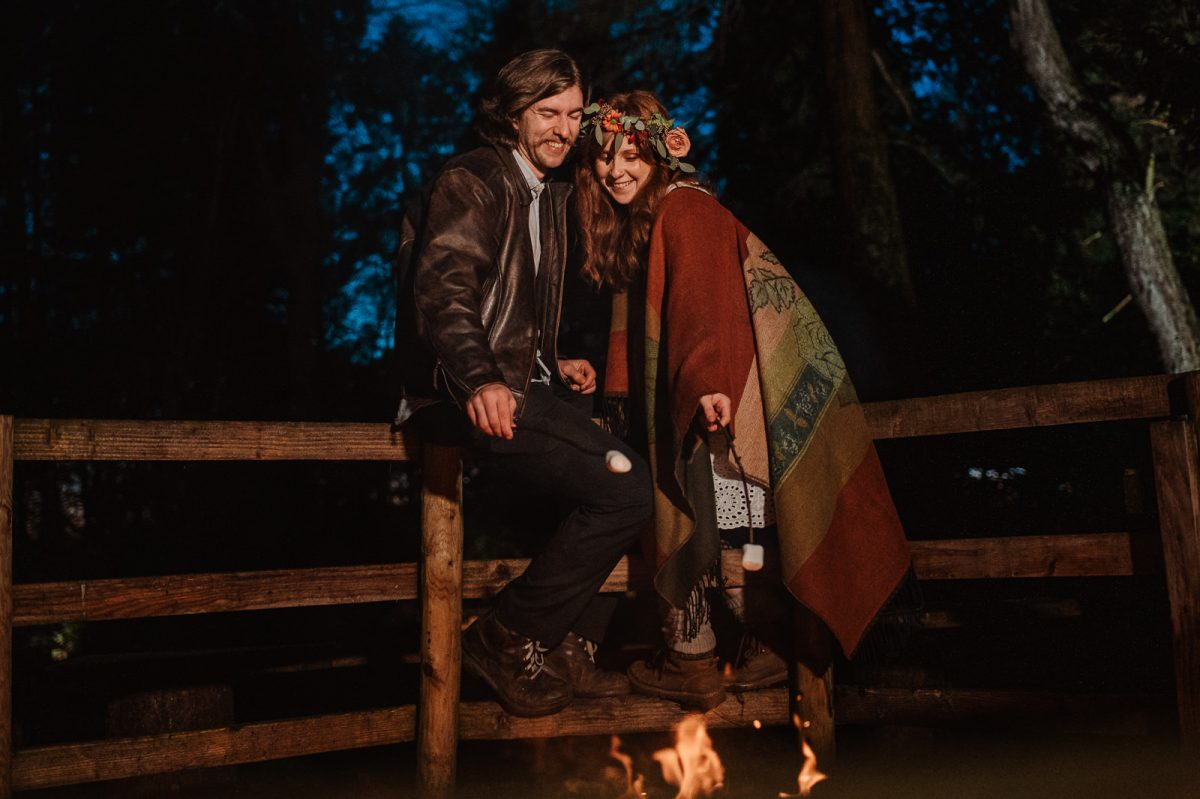 Couple roasting marshmallows in front of the fire camp to celebrate their elopement wedding