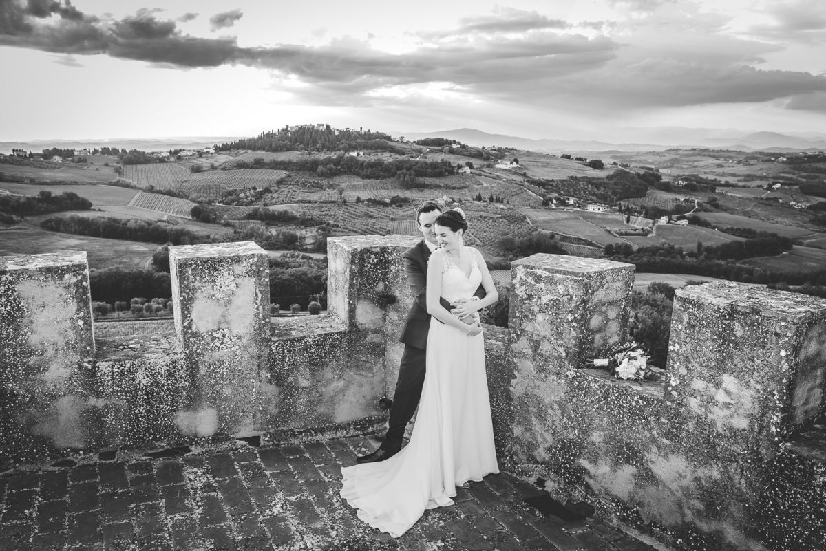 Couple hugging at the top of a castle tower. Fields in the background