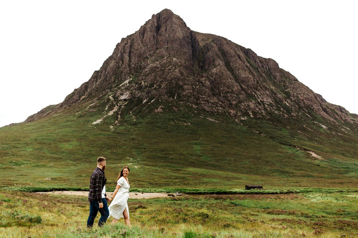 Photo of a couple walking surrounded by nature in Scotland for their couple session