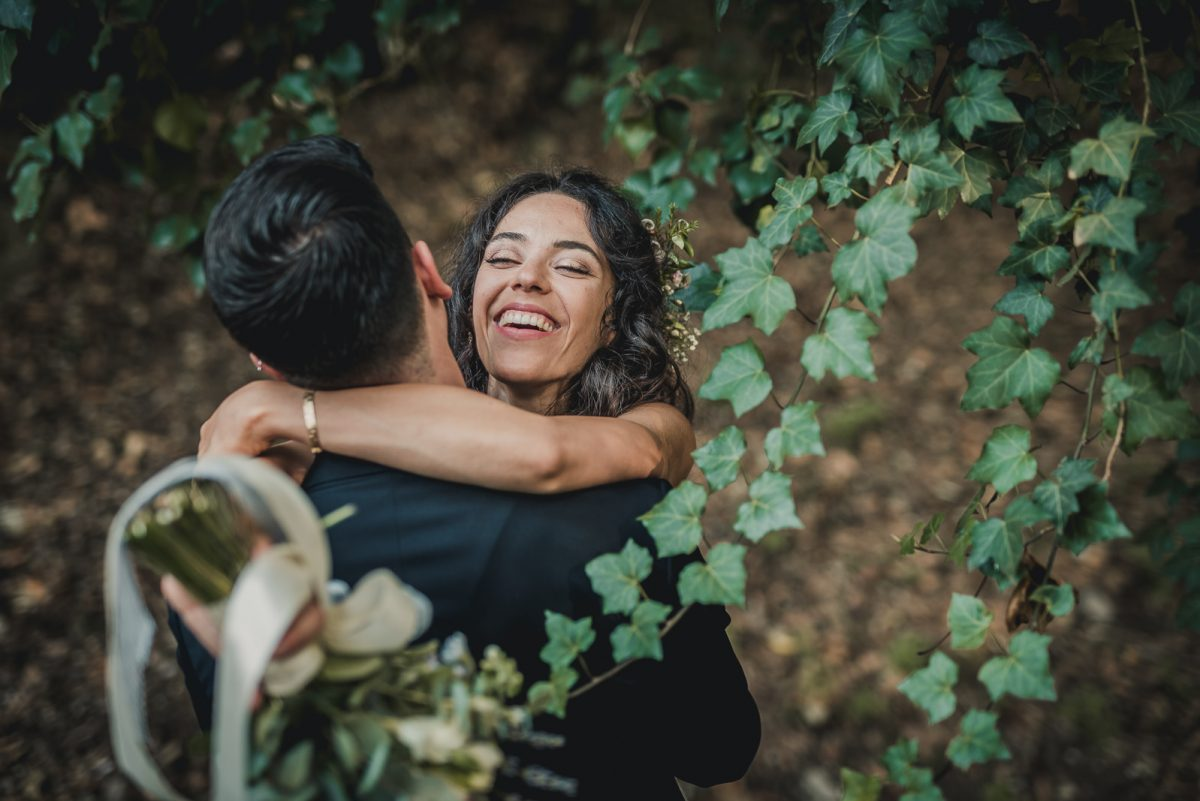 Just married couple having fun. The bride is smiling while the groom hold her. An ivy plant is framing them on the side