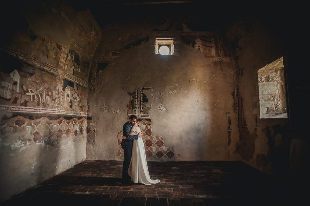 Couple hugging inside an ancient room in a Castle in Italy