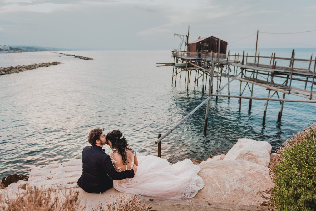 Eloping couple. They are sitting on a cliff enjoying the sea view