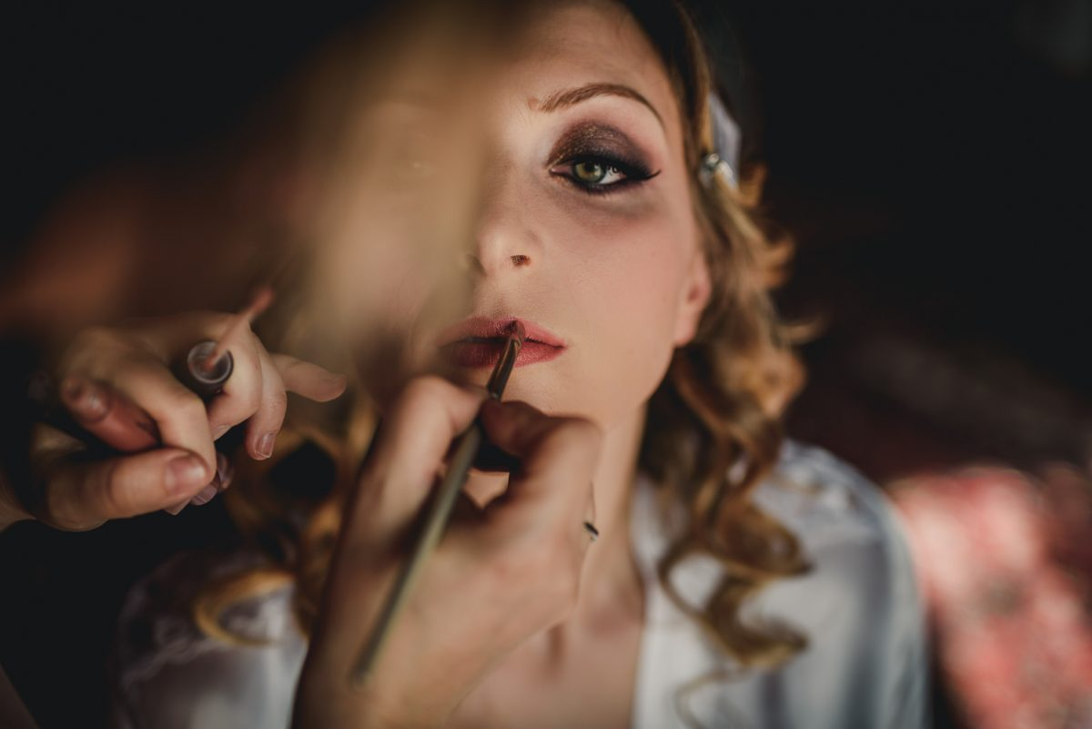 A portrait of a bride getting ready for her wedding. Detail of the brush retouching her lips