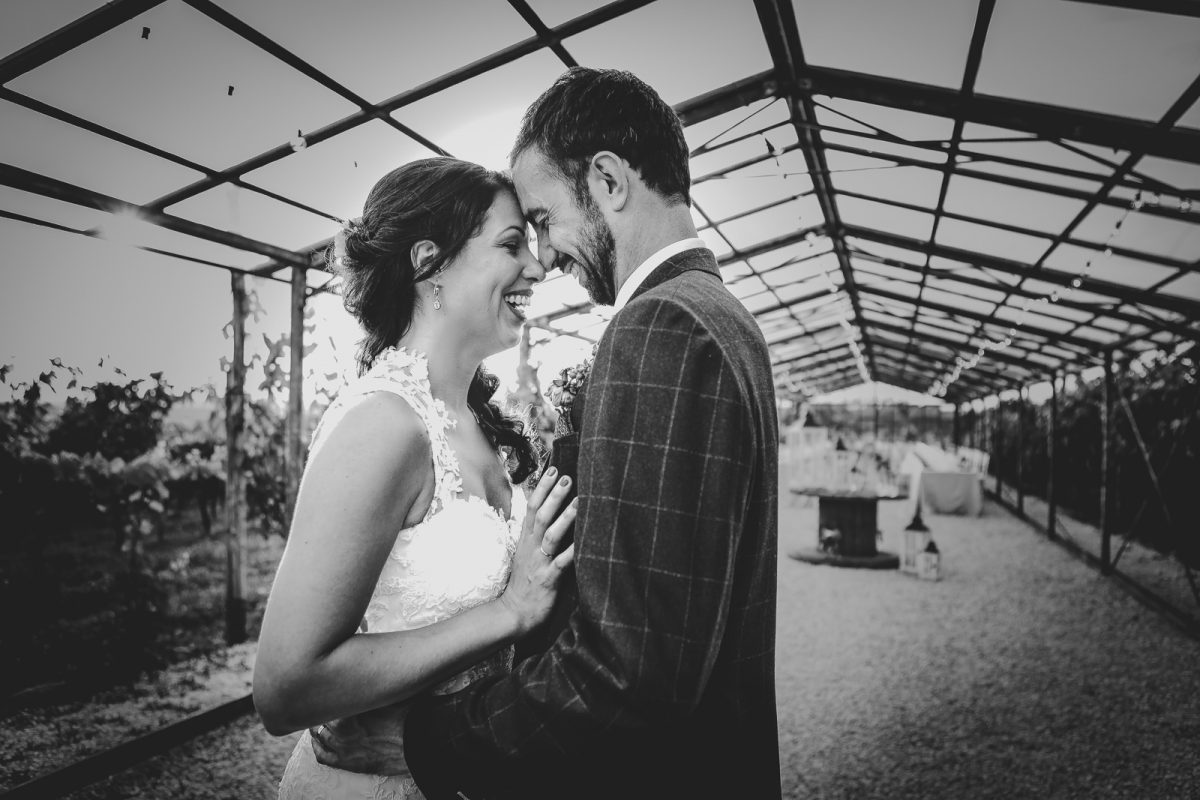 Couple laughing and smiling inside a greenhouse used as reception location