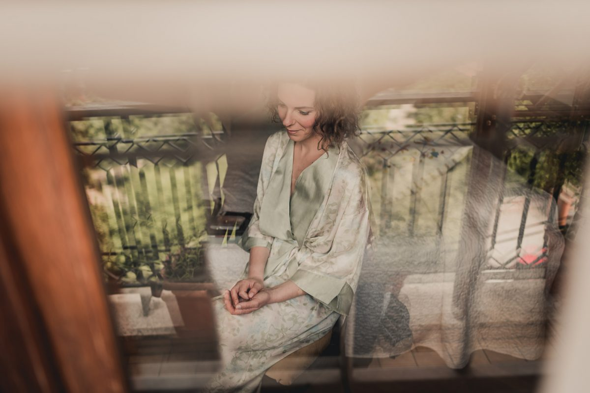 Photo of a bride sitting for her getting ready. She is wearing a green silk robe. Shot taken behind a window