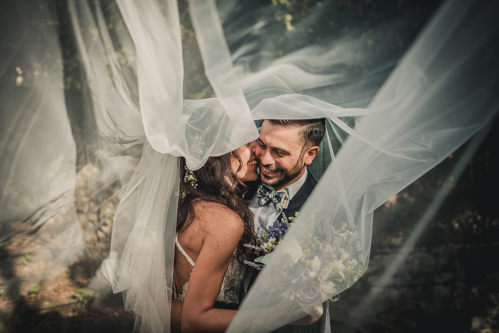 Couple laughing and hugging each other under the bride veil.