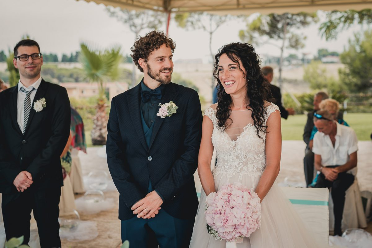 Couple smiling during their ceremony. The bride has a delicate pink bouquet, and a boho wedding dress.