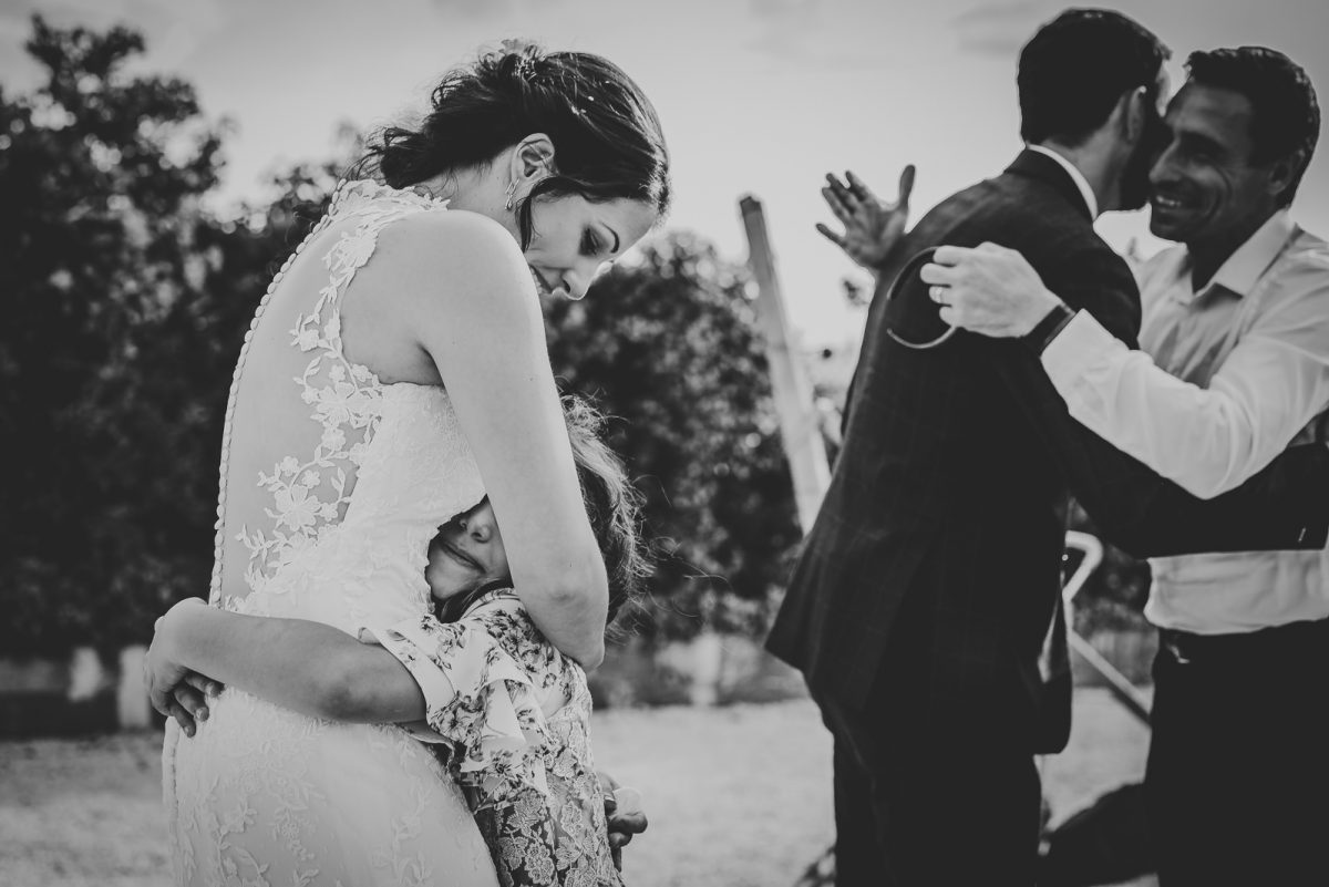 Black and white portrait of bride and groom celebrating with their family. The bride is a hugging a kid