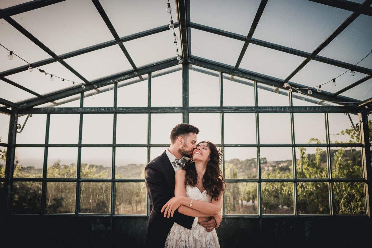 Groom hugging bride during their wedding day. The couple is standing under a greenhouse, there are some fairy lights surrounding them. A vineyard in the background