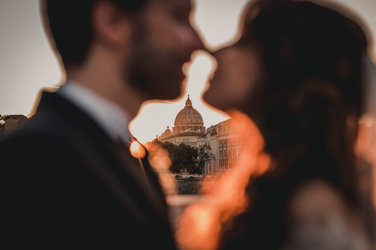 Photo showing a couple kissing with S. Peter Church in the background