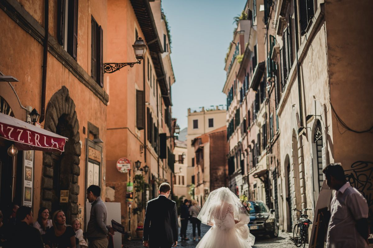 Just married couple walking in a famous street in Trastevere Rome. The sun is shining, there is a blue clear sky, and the light is gently lighting the houses