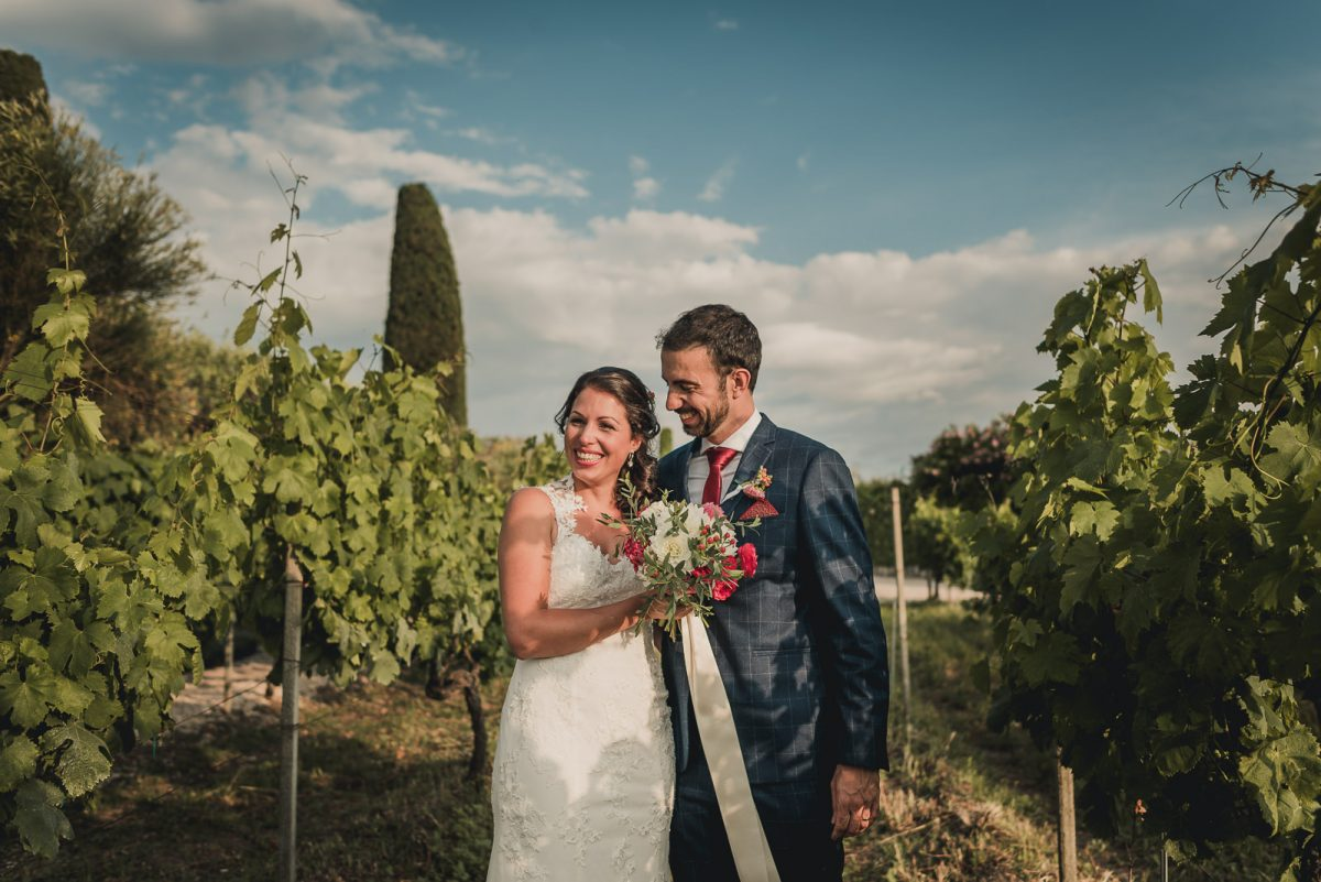 Couple walking through a vineyard in Rome. The bride has a boho wedding dress, with a delicate bouquet.