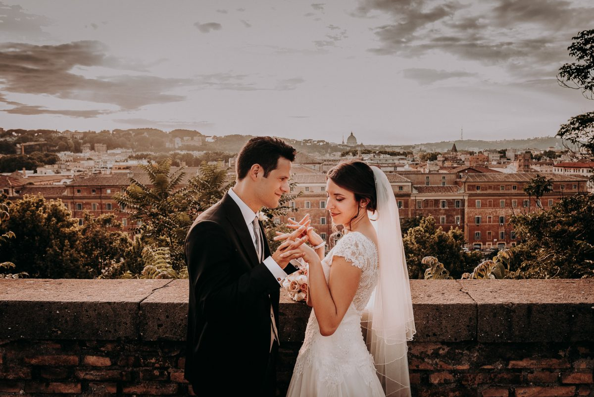 Couple enjoying the view of Rome at sunset. They are gently playing with their hands, and smiling