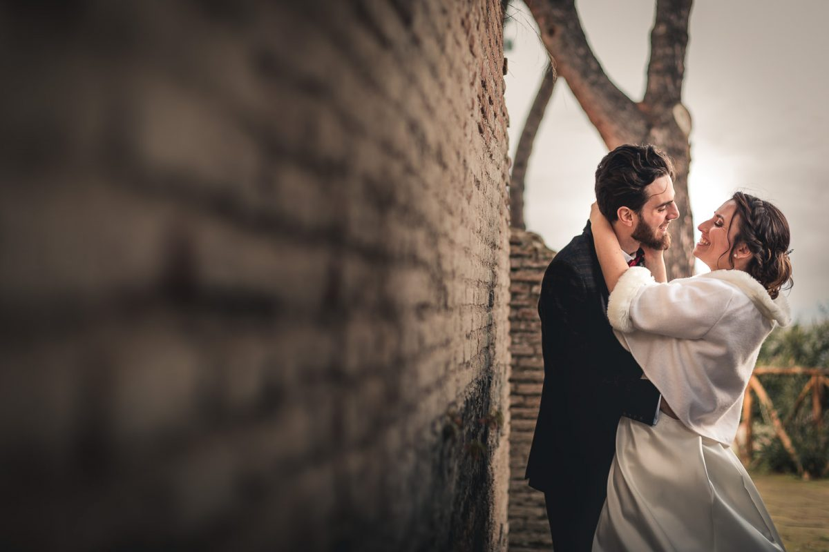 Couple hugging and smiling while they look at each other. They are close to an ancient wall in Rome. The bride is wearing a lovely white winter coat. The groom wears a British attire