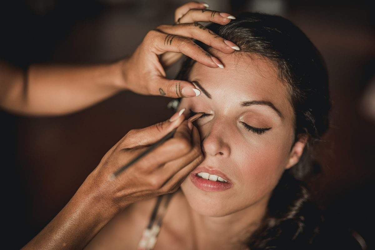 Portrait of a bride while she is doing her make-up. Details of the make-up artist hands retouching her eyes