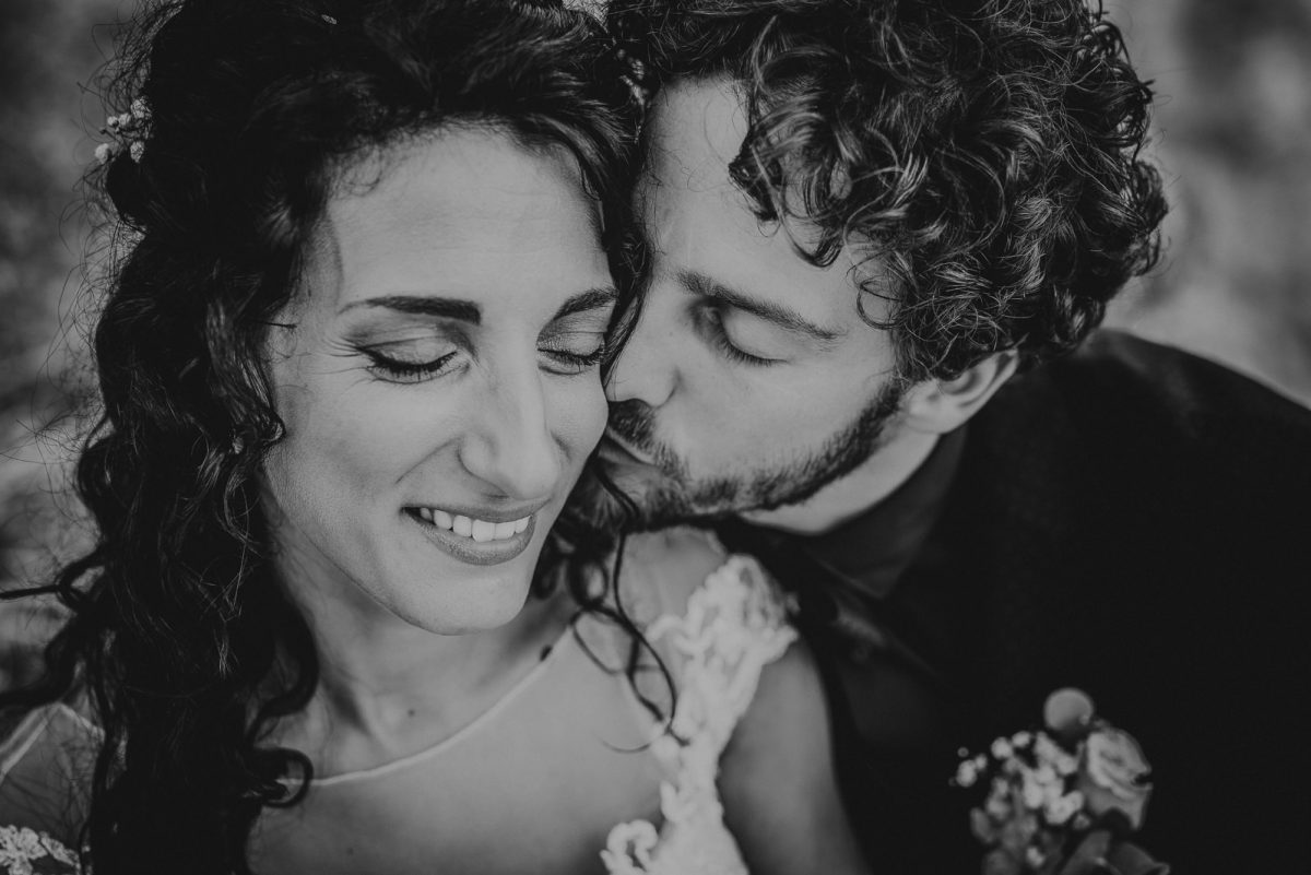 Black and white portrait of a couple. The groom is kissing the bride cheeck.