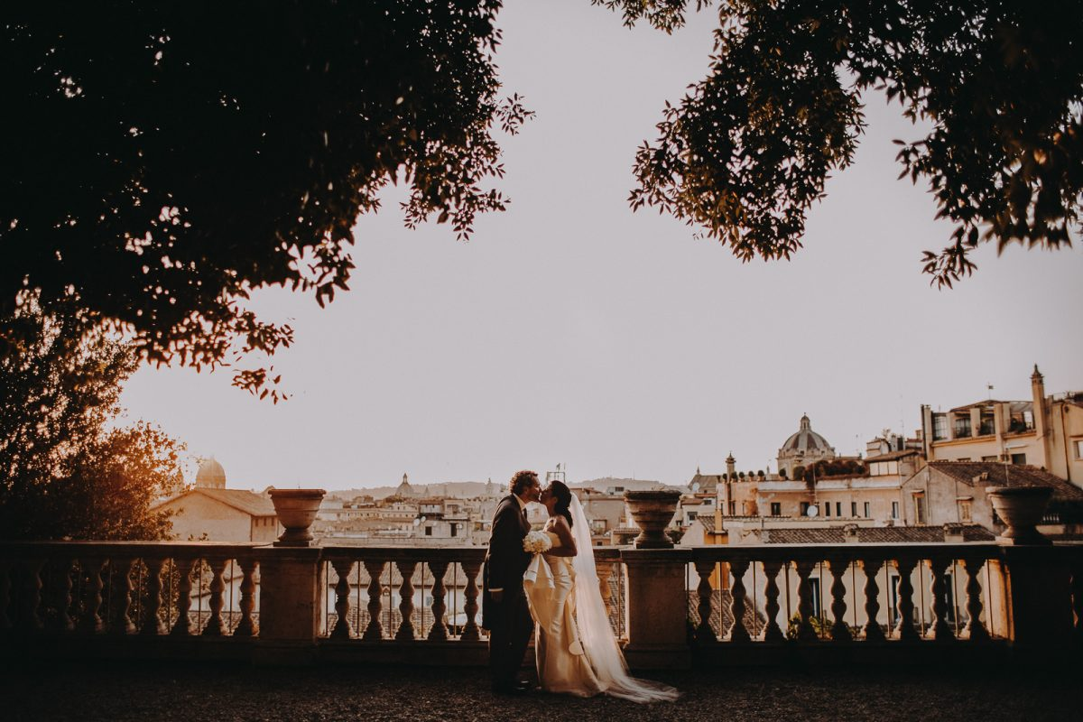 Couple kissing and enjoying the view from the top of a viewpoint in Rome at sunset.