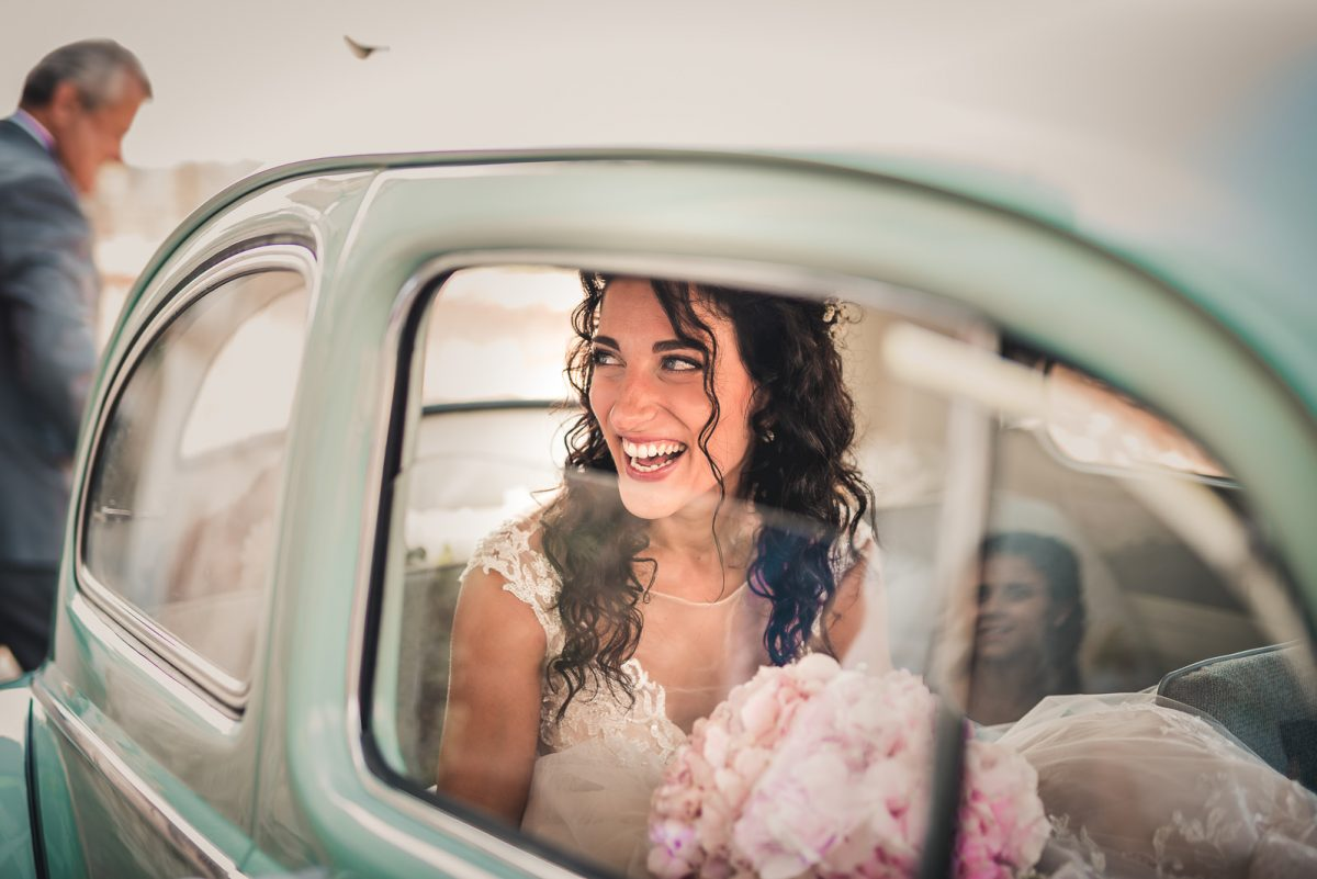Bride smiling inside an old fiat car. She has a delicate pink bouquet, and a simple sleek with waves.