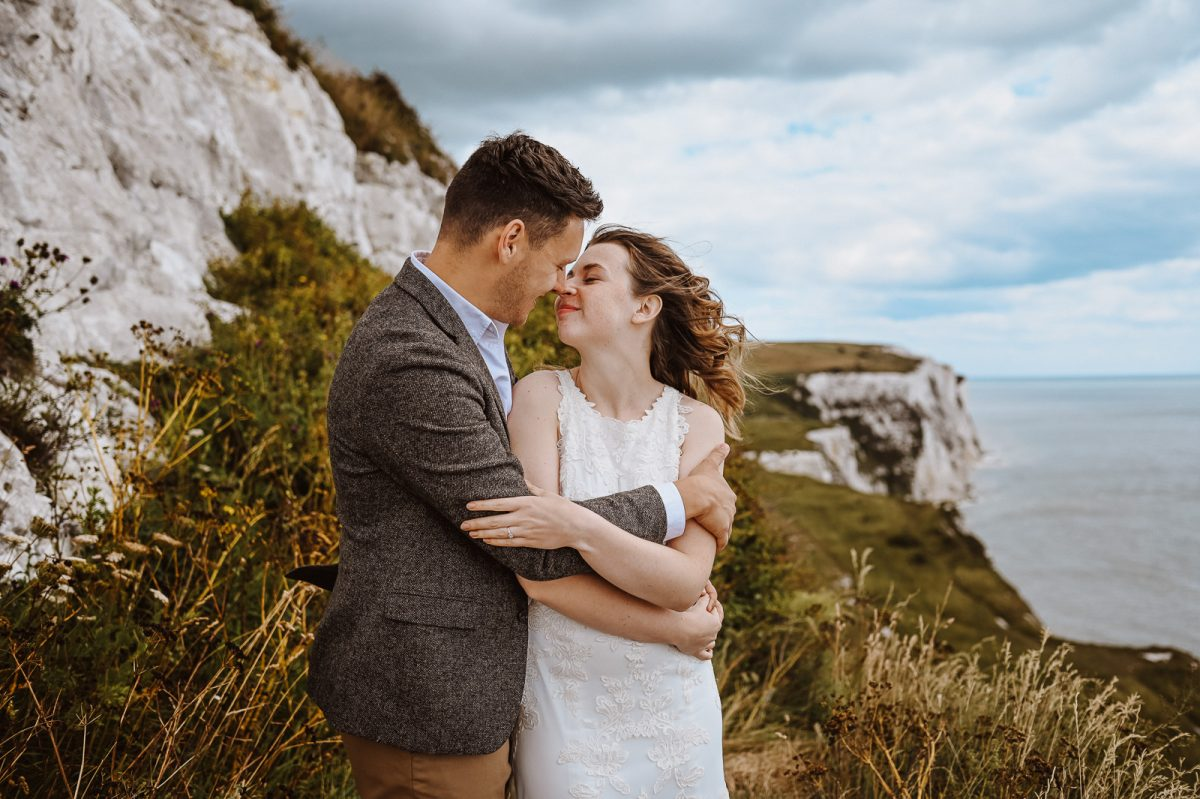 Couple hugging on the top of a Cliff in Kent. The bride is wearing a lovely boho wedding dress, by Maggie Sottero. The groom is wearing a casual jacket with grey shades