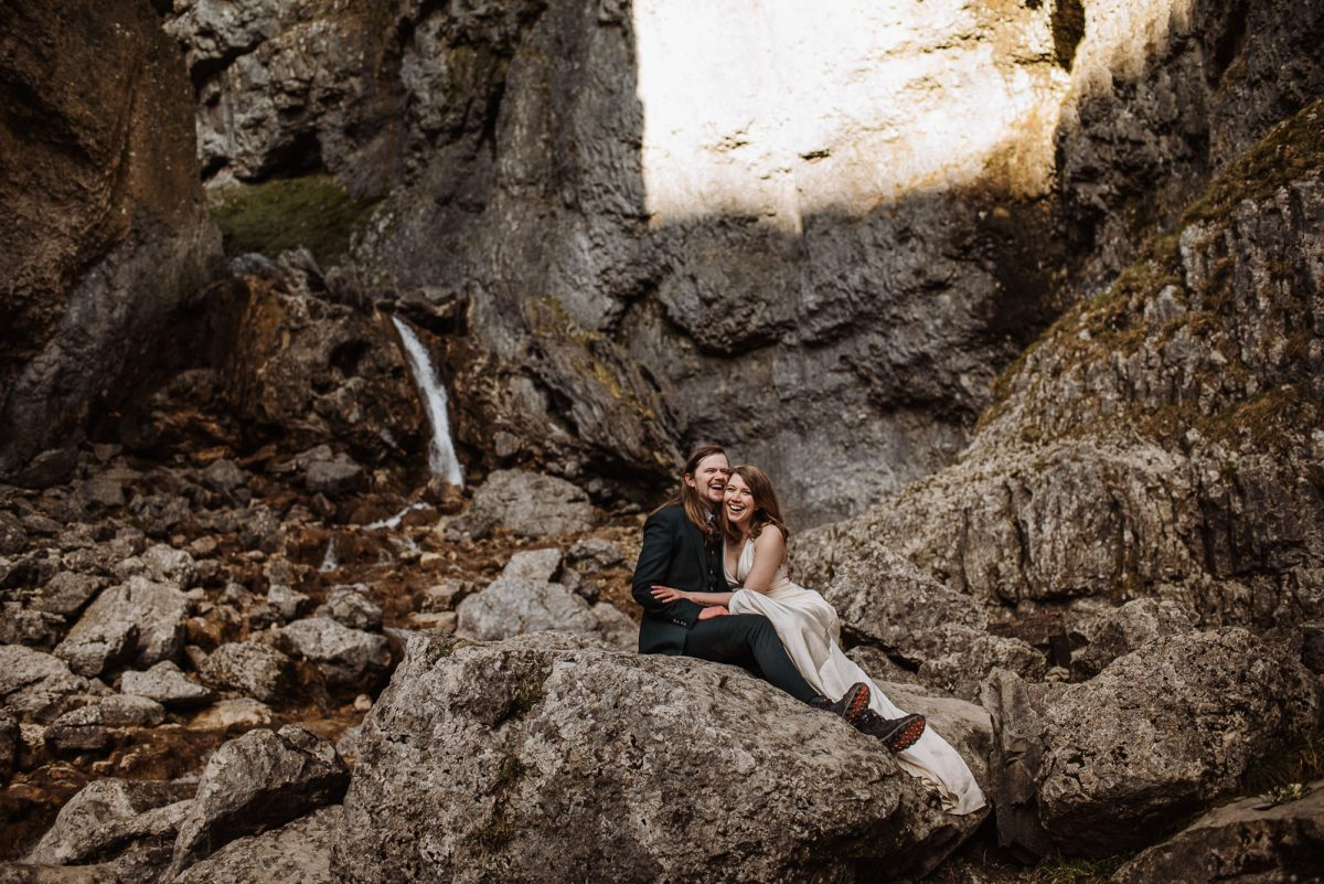 Couple sitting and cuddling, with waterfalls in the background