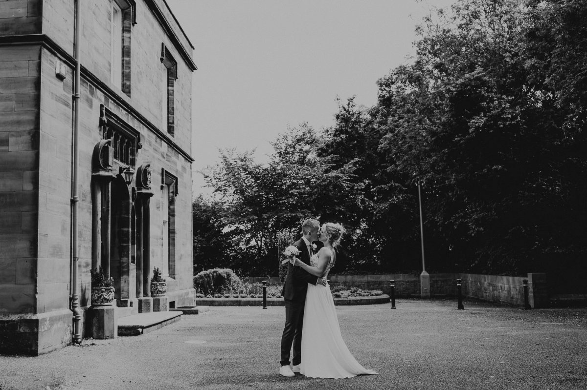 Small wedding in Lake District. Couple kissing in front of the register office.