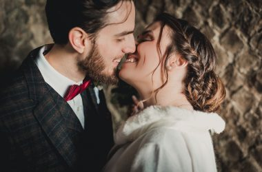 Close portrait of a couple smiling and kissing. The bride wears a winter white coat. The groom wears a British attire